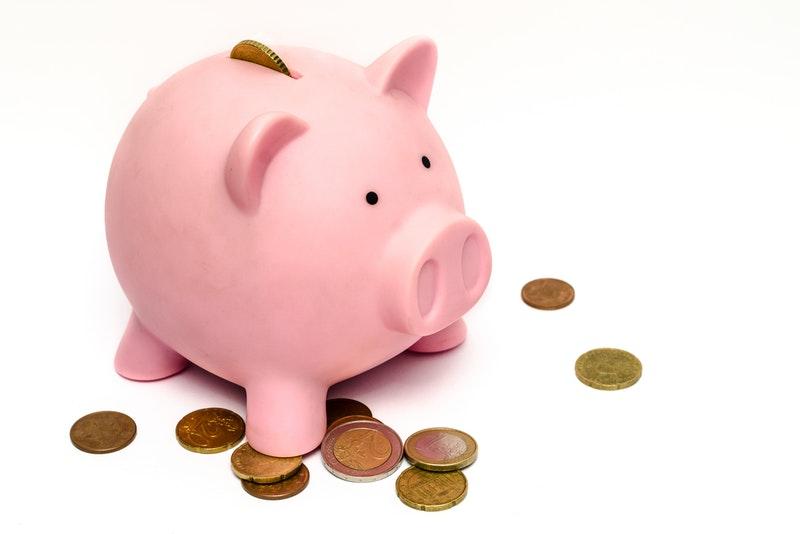 豚の貯金箱と散らばる硬貨